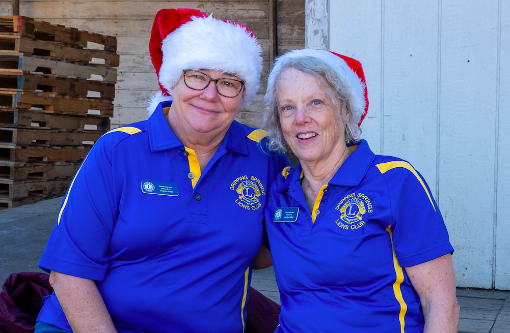"""Sharon Goss and Marilyn Miller from Dripping Springs Lions Club get in the seasonal spirit during """"Christmas on Mercer"""", Saturday, December 7th, 2019. Photo by Dave Wilson."""