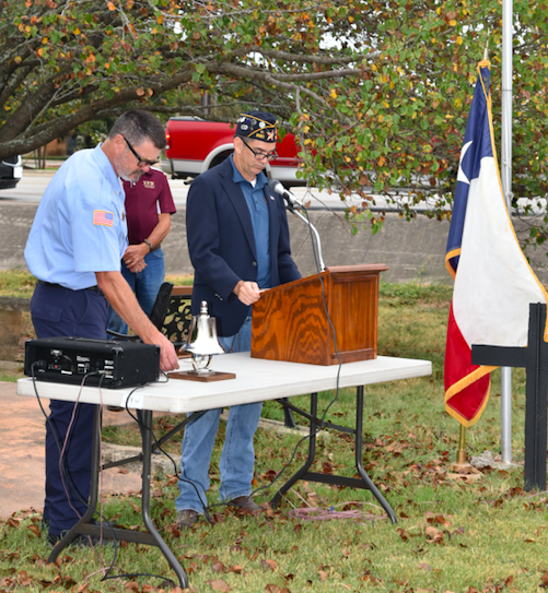 "North Hays Firefighter Mark Treadway rings ""four fives bells"" to honor the fallen firefighters of 9/11. American Legion Commander Ben Adair stands at the podium."