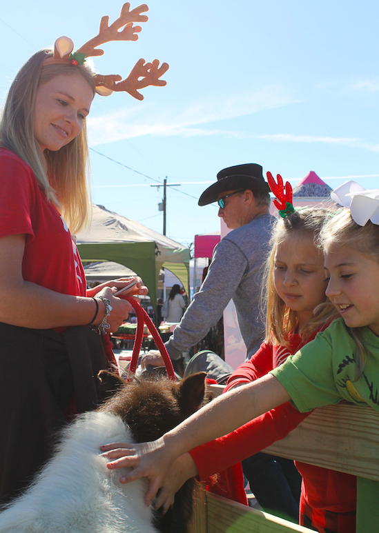 Claire Clements and Addison Griffin meet one of the ponies from Red Arena and helper Kendall Randow during Christmas on Mercer in Dripping Springs, Saturday, December 7th, 2019. Photo by Haley Henry.