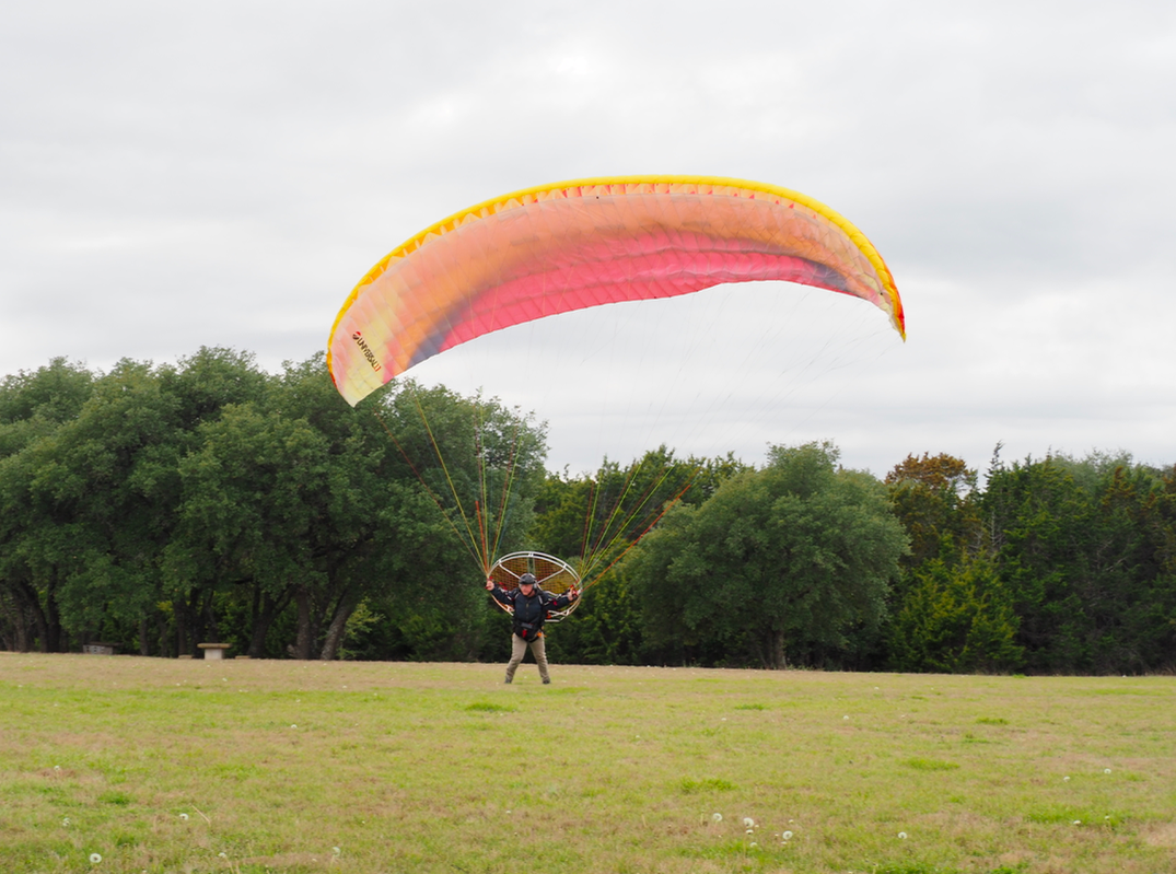 He cautiously walks forward, permitting the Paraglider to begin lifting him off the ground.