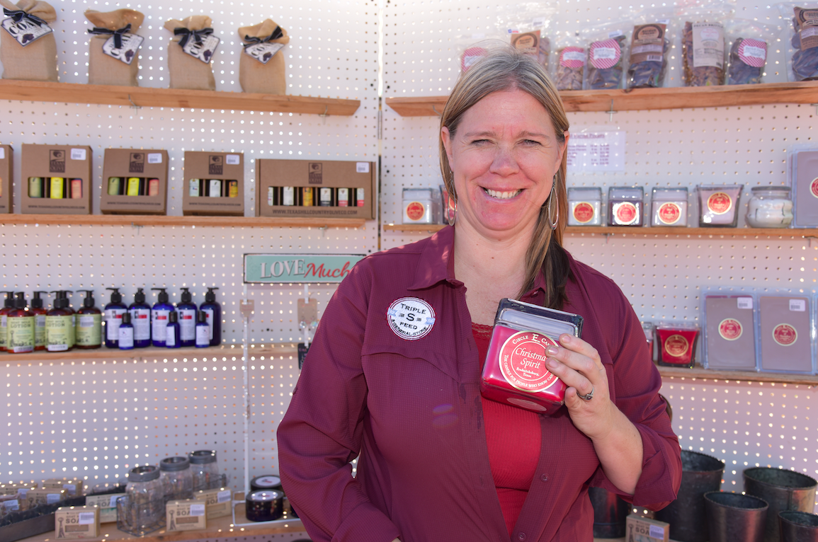 "Monica Swenson, owner of Triple ""S"" Feeds, holds up a Circle E Candle from Fredericksburg, as a Christmas stocking stuffer idea. ""We are locally owned, and we support local businesses,"" she said."