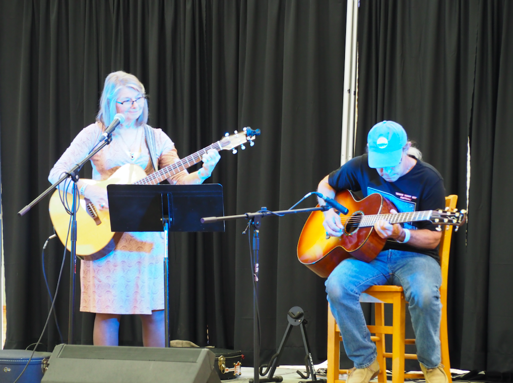 ": Martha Pinto and her husband, Jamie Kinscherff, performed ""Americana folk music,"" on the festival music stage. Kinscherff is owner of Kinscherff Guitars, a local company that sells hand-made acoustic guitars, kinscherff.com"